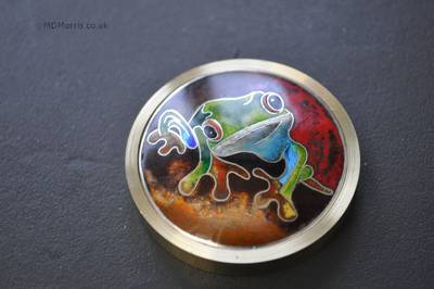 angled view of the cloisonné frog sitting in the ring